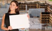 Beautiful woman smiling and hold empty paper sheet. Construction site as backdrop — Stock Photo