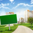 Buildings, green hills and road with empty roadsign against sky — Stock Photo #58279421