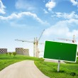 Industrial zone, green hills and road with empty roadsign against sky — Stock Photo #58279639