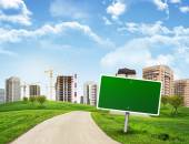 Buildings, green hills and road with empty roadsign against sky — Stock Photo