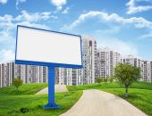 Tall buildings, green hills and road with large billboard against sky — Stock Photo