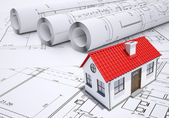 Small model house with red roof near scrolls of architectural drawings — Stock Photo