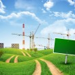 Industrial zone, green hills and road with empty roadsign against sky — Stock Photo #58323111