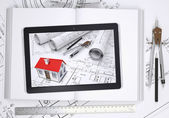 Small house with drawings displayed on tablet screen. Open book and tools of architect — Foto de Stock