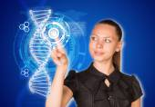 Beautiful businesswoman in dress smiling and presses finger on model of DNA — Stock Photo