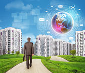 Businessman walking along road through green hills towards city. Brightly coloured planet, charts and other virtual items in sky — Stock Photo