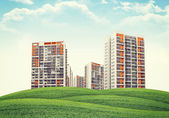 High-rise buildings over green hills — Stock Photo