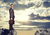 Businessman standing on the edge of rock gap — Stock Photo