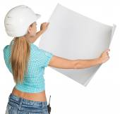 Beautiful woman builder holding in front of him large paper sheet. Rear view — Stock Photo