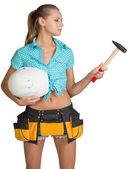 Pretty girl in tool belt holding white helmet and hammer — ストック写真