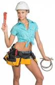 Pretty girl in helmet, shorts, shirt, tool belt with tools holding flexible hose and wrench — Stock Photo