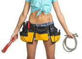 Plumber in shorts, shirt, tool belt with tools holding flexible hose and wrench — Stock Photo