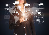Businesswoman touches future style sensor screen on which there is map of the world — Stock Photo
