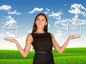 Businesswoman holding two houses as if chosing — Stock Photo