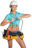 Pretty girl in helmet, shorts, shirt and tool belt with tools connects two flexible hose for plumbing — Stock Photo