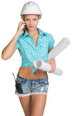 Beautiful girl in white helmet, shorts with shirt holding scrolls drawings and talking on phone — Stock Photo