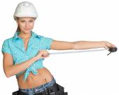 Beautiful girl in white helmet, shorts and shirt holding tape-measure — Stock Photo