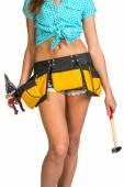 Woman wearing shirt, shorts and tool belt, holding hammer — Stock Photo