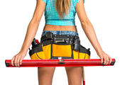 Woman wearing tool belt with tools holding builders level, close up — Stock Photo