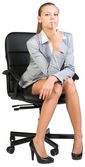 Businesswoman on office chair holding forefinger at her lower lip — Stock Photo