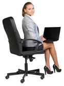 Businesswoman on office chair, with laptop — Stock Photo