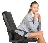 Businesswoman on office chair, with head reclined upon her hands — Stock Photo