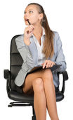 Businesswoman sitting on office chair with clipboard and pen — Stock Photo