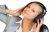 Businesswoman in headset with her hands on speakers — Stock Photo