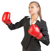 Businesswoman wearing boxing gloves, her lips parted — Stock Photo