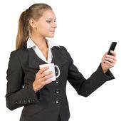 Businesswoman holding mug and using mobile phone — Stock Photo