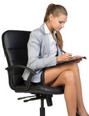 Businesswoman sitting on office chair with clipboard and writing — Stock Photo