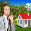 Businesswoman in headset, small house and green landscape as backdrop — Stock Photo #63896239