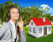 Businesswoman in headset, small house and green landscape as backdrop — Stock Photo