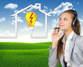 Businesswoman in headset, symbol of home energy supply and service beside — Stock Photo
