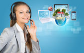 Businesswoman in headset, Globe, computers, smartphone and network beside — Stock Photo