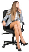 Businesswoman on office chair with her finger under chin, looking upwards — Stock Photo