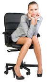Businesswoman on office chair with head reclined upon her hands — Stock Photo
