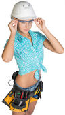 Woman in hard hat, tool belt and protective glasses — Stock Photo