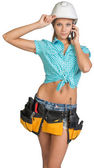 Woman in hard hat and tool belt calling on mobile phone — Stock fotografie