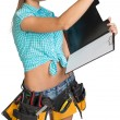 Woman in hard hat and tool belt writing on blank clipboard — Stock Photo #64009679