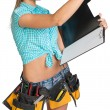 Woman in hard hat and tool belt writing on blank clipboard — Stock Photo #64188179