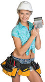 Woman in hard hat and tool belt showing calculator — Stock Photo