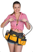 Woman in tool belt holding flexible tap hose — Stock Photo