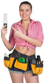 Woman in tool belt holding energy-saving lamp — Stock Photo