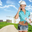 Woman in hard hat, holding drawing rolls calling on the phone — Stock Photo #64384199