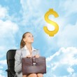 Businesswoman sitting on office chair, looking up at dollar sign in the air — Stok fotoğraf #64384547