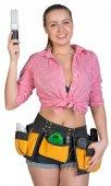 Woman in tool belt holding energy-saving lamp — Stock Photo