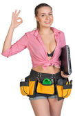 Woman in tool belt, with laptop under her armpit, showing okay sign — Stock Photo