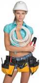 Симпатичный электрик в шлеме, шортах, рубашке, поясе инструмента с инструментами, держащими электрический кабель — Стоковое фото