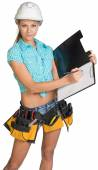 Woman in hard hat and tool belt writing on blank clipboard — Stock Photo